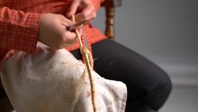 View of craftsman cleans twig from bark. Basketry. View of craftsman cleans twig from bark stock footage