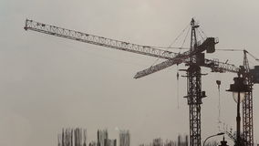 View of cranes over building construction. Panorama of cranes over building construction at dawn stock footage