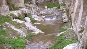 View on creek flowing among stones and ruins stock footage