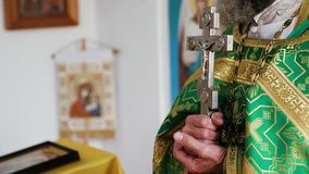 A view of a cross in hands of a priest, saying the prayer. In a church stock footage