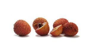 A view of the cross-section of a lychee fruit with seed, next to whole fruits. For dessert royalty free stock photography
