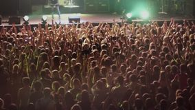 View of crowd people raise hands on rock concert in nightclub. Band performing on stage. stock video footage