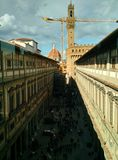 View of the crowded courtyard from the windows of Uffizi Gallery with a construction crane, the Cathedral dome and clock tower of stock photography