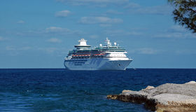 View of Cruise Ship Anchored off Island Shore Stock Photo