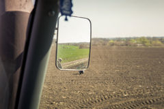 view of cultivator in upper backside mirror in tractor cabin Royalty Free Stock Photo
