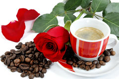 View of a cup of coffee with a red rose and coffee beans on whit Stock Image