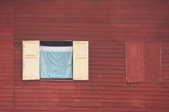 View of curtain and wooden window on red wall of wooden house at countryside. View of curtain and wooden window on red wall of wooden house at countryside in Royalty Free Stock Photography