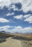 View of curved road among snow capped mountains Royalty Free Stock Photos