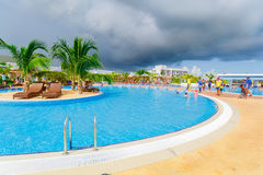 View of a curved wide open comfortable swimming pool with entertainment team and people enjoying their time on sunny gorgeous day Royalty Free Stock Photography