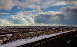 View of a curving road covered in snow way road during winter time, snow mountains in the distance. View of a curving road covered in snow way road during winter royalty free stock image