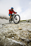 View of cyclist riding mountain bike on trail in Dolomites,Tre C Royalty Free Stock Images