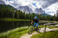 View of cyclist riding mountain bike on trail in Dolomites,Tre C Stock Photos
