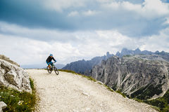 View of cyclist riding mountain bike on trail in Dolomites,Tre C Stock Photo
