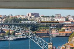 View of D. Luis bridge, with two subways to cross at the top, Douro river with boats and Vila Nova de Gaia city as background stock photo