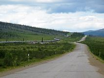 View of Dalton Highway with oil pipeline, leading from Valdez, Fairbanks to Prudhoe Bay, Alaska, USA. View of Dalton Highway with oil pipeline, leading from Stock Photo