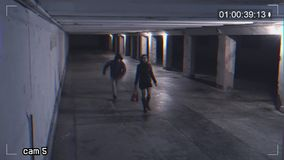 Robbing a girl in an underpass. Recording from a surveillance camera. View of dangerous situation in the underpass stock footage