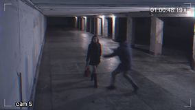 Robbing a girl in an underpass. Recording from a surveillance camera. View of dangerous situation in the underpass stock video footage