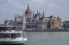 View of Danube River and Hungarian Parliament Building with ferry boat Stock Photography