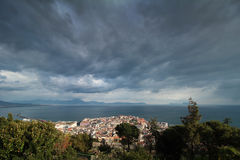 View of dark clouds above Naples. Dramatic sky above the sunny italian city. In the background can be seen Capri Island and the italian mountains on the coast Royalty Free Stock Images