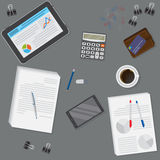 View of dark office desk including tablet, smartphone, financial and business objects. Royalty Free Stock Photography