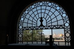 View from the dark room of the monastery of the Virgin through metal grid with a cross to the Golden Dome of the Rock, Jerusalem,. View from the dark room of the Royalty Free Stock Image