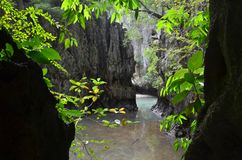 View from the darkness of the Ice cream cave on a mountain and lake among the greenery. Phang Nga province, Thailand. Photo framed by shadow and foliage of stock image