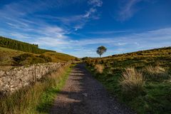 View of Dartmoor from the path to Wistmans Wood. A view of Dartmoor from the path to Wistmans Wood on a sunny September day with blue sky and clouds royalty free stock photography