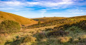 View of Dartmoor from the path to Wistmans Wood. A view of Dartmoor from the path to Wistmans Wood on a sunny September day with blue sky and clouds royalty free stock photo