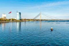 View of Daugava River with cable-stayed bridge, Latvian flag and boat that crosses the river, Riga. Royalty Free Stock Photography