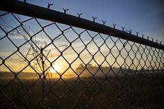 View of dawn from behind a fence. Each dawn represents a day of new opportunities and challenges Royalty Free Stock Photography