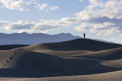 View from Death Valley Dunes. Man taking in the views in Death Valley's Sand Dunes. Foot prints leading up a large sand dune to a man. Death Valley stock photo