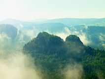 View into deep misty valley in Saxony Switzerland. Sandstone peaks increased from heavy colorful fog. Royalty Free Stock Images