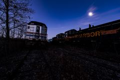 Derelict Locomotives at Twilight - Abandoned Railroad Trains. A view of a derelict Amtrak and Indiana Harbor locomotive at twilight at an abandoned train Royalty Free Stock Photo