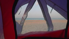 View of deserted beach and blue sea through little window in tent. View of deserted beach and blue sea through little window in touristic tent stock video footage