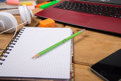 View on desk top workspace. View on college student desk top workspace with note pad with lap top pencil and headphones on desk Royalty Free Stock Images