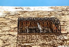 View of detail of stone building with typical Mediterranean arabic style window and balcony with ornament old forging in Medina. View of detail of stone Stock Photos