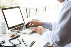 View of Details of doctor hands typing on keyboard with blank sc royalty free stock image