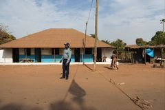 View of a dirt road in a street of a slum in the city of Bissau with a police officer standing in front of a house, in Guinea-Biss. Bissau, Republic of Guinea royalty free stock photo