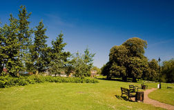 View of Diss Park in Summer. A view of Diss Park in summer showing the benches and public footpath . Taken in Diss Norfolk East Anglia England United Kingdom royalty free stock photo