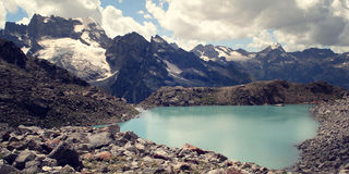 View of Distant Peaks. Bright blue water in the alpine lake. Stock Images