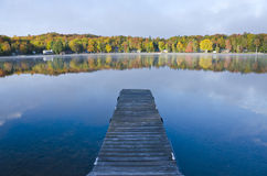 View of a Dock and Colorful Trees on the Lake Stock Image