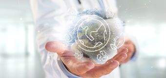Docotor holding a World globe surronding by ecology icons and connection 3d rendering. View of a Docotor holding a World globe surronding by ecology icons and stock image