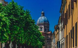 View of dome of the Church of St. Barnabas in downtown Mantua, I. View of dome of the Church of St. Barnabas above houses and trees in downtown Mantua, Italy stock photos