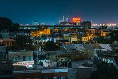 View of the Domino Sugars Factory and houses in Federal Hill at night, in Baltimore, Maryland stock image