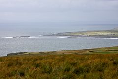 Panoramic view of Doolin village with the pier, county Clare, Ireland. View of Doolin village and the small island at the entrance of Doolin`s Bay, The Burren royalty free stock images