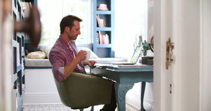 View Through Door Showing Man Working In Home Office. View through doorway of man using laptop sitting at desk in home office - he pauses to drink cup of coffee stock video