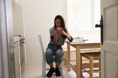 View from doorway of girl messaging on smartphone in kitchen Stock Images