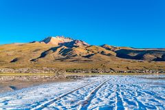 View of the dormant volcano Tunupa and the village of Coqueza at the Uyuni Salt Flat. In Bolivia stock image