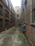 View down a long alley between brick industrial buildings. Vertical aspect stock image