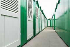 Green painted beach cabins with white doors. View down a row of green painted wooden beach cabins with white doors stock images
